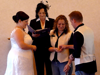 Donna from England & Bridget exchange rings at their Commitment Ceremony in the chapel at the Crowne Plaza in Surfers Paradise on the Gold Coast. Danny Donna's best man hands her the rings.
